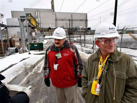 """In this picture, Exelon's Pete Tamburro, left, and David Benson stand outside the Oyster Creek nuclear plant, background, in Lacey Township, N.J. Spokesman Benson said the reactor """"is as safe today as when it was built."""" Yet plant officials have been trying to arrest rust on its 100-foot-high, radiation-blocking steel drywell for decades. The problem was declared solved long ago, but a rust patch was found again in late 2008. Benson said the new rust was only the size of a dime, but acknowledged there was """"some indication of water getting in"""