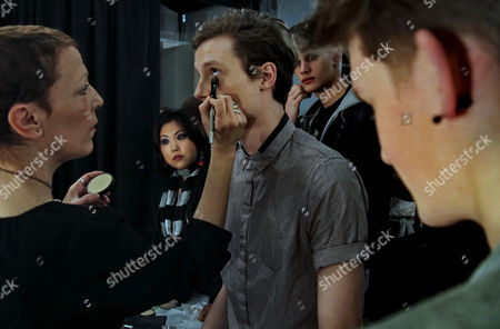 Dawn Dioreo, left, places makeup around the eye of Matthew Hitt, center, before he models fashion from Yigal Azrouel fall 2010 collection, during Fashion Week in New York