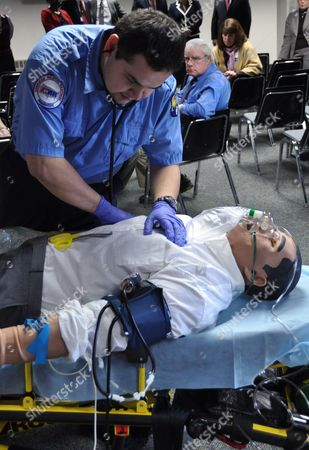 """Stock Photo of Sean Devine, a paramedic with American Medical Response, checks on """"Stan,"""" a human patient simulator, in Pierre, S.D. Rural South Dakota emergency medical workers are getting access to the training simulators thanks to a $5.6 million grant from the Leona M. and Harry B. Helmsley Charitable Trust"""