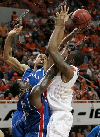 James Anderson, Sherron Collins, Xavier Henry Oklahoma State guard James Anderson, right, attempts a shot while guarded by Kansas guard Sherron Collins, left, and guard Xavier Henry, center, during the first half of an NCAA college basketball game in Stillwater, Okla