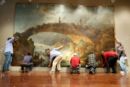 "Simon Parkes, third from left, owner of Simon Parkes Art Conservation, and his associates lift the oil painting ""Le Pont Sur Le Torrent,"" by Hubert Robertís off the ground, in New York. The 20 feet wide and 13 feet tall painting originally commissioned circa 1780 and formerly owned by newspaper baron William Randolph Hearst will be on public view from January 23rd through the 28th at Christie's New York and be sold on the 27th"