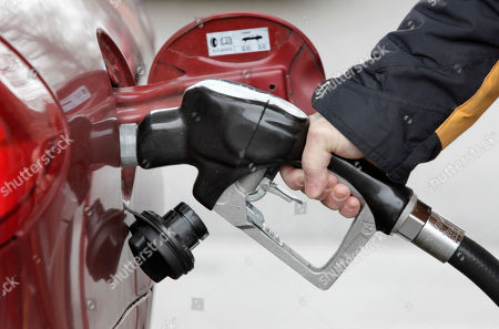 Michael Lerner pumps gas into his car at the Speedway gas station in Cleveland Hts., Ohio. Oil prices slid well below $75 a barrel Tuesday, Jan. 26, weighed by weaker stock markets in Europe and Asia and a stronger dollar