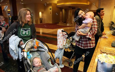 Christy Lemire, Teresa Strasser New moms Christy Lemire, left, and Teresa Strasser, right, wait in line with their babies for popcorn before attending a special movie screening held once a week just for moms, their babies and young children, in Los Angeles