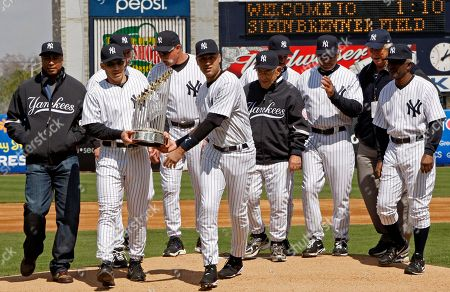 Bernie Williams, Joe Giardi, Tino Martinez, Goose Gossage, Derek Jeter, Yogi Berra, Ron Guidry, Reggie Jackson, Gene Michael Mickey Rivers Old time Yankees watch as New York Yankees manager Joe Girardi, second from left, and Yankee captain Derek Jeter carry the World Series trophy from the mound following a pregame ceremony before th Yankees home spring training baseball opener against the Pittsburgh Pirates at Steinbrenner Field in Tampa, Fla., . From left are Bernie Williams, Joe Giardi, Tino Martinez, Goose Gossage, Derek Jeter, Yogi Berra, Ron Guidry, Reggie Jackson, Gene Michael and Mickey Rivers