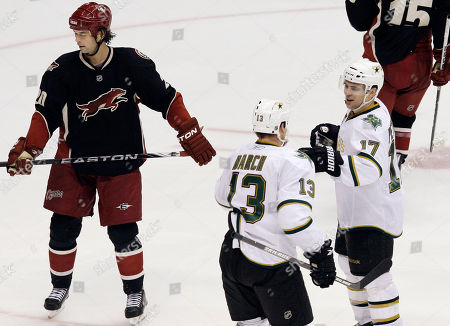 Stock Photo of Toby Petersen, Krys Barch, Robert Lang Dallas Stars' Toby Petersen (17) celebrates his goal with teammate Krys Barch (13) as Phoenix Coyotes' Robert Lang, left, of the Czech Republic, skates past in the third period of an NHL hockey game, in Glendale, Ariz. The Stars defeated the Coyotes 3-0