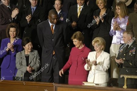 Dikembe Mutombo, Centre for the Houston Rockets, attends the State of the Union address. Mutombo recently became a US citizen and was cited by the President during his speech. Standing next to him on the left (in the blue dress) is Ambassador Nancy Brinker and Dr. Nancy Ho and on the right Laura Bush (in the red dress) and Lynn Cheney (in white)