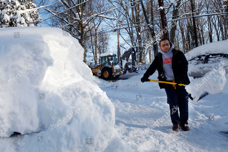 "As a plow passes by, John Ibrahim digs out his car at his home that has been without power since Friday night in Silver Spring, Md. on . A massive snow storm hit the region Friday and Saturday, dumping 2 feet of snow in some places. ""At least if we clean off the cars we can get some heat and charge the cell phones,"" says Ibrahim"
