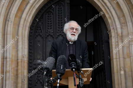 British former Archbishop of Canterbury Rowan Williams speaks to the media about the migrant children who will be resettled in the UK, outside Croydon Minster church, in Croydon, south London, . Fourteen children who have been living in a border refugee camp in northern France are due to arrive in Britain to be reunited with their families. Williams says the children will register at a government building in south London Monday before being reunited with relatives at local churches