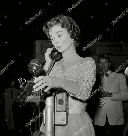 Stock Photo of Actress Jean Simmons takes a call on a sound stage phone between takes while making ?This Earth of Mine? in October 1958 in Hollywood