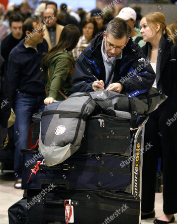 Barry Jones, from Windsor, Ont., Canada fills out luggage tags as he waits in line at the Delta Airlines counter in the Detroit Metropolitan Airport, in Romulas, Mich