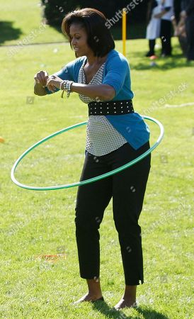 Michelle Obama First lady Michelle Obama as she exercises with a hula hoop during a healthy kids fair on the South Lawn of the White House in Washington. Wearing a belt, even if it doesn't sit on the natural waistline, can help add feminine shape to an athletic body type, according to Adam Glassman of O The Oprah Magazine
