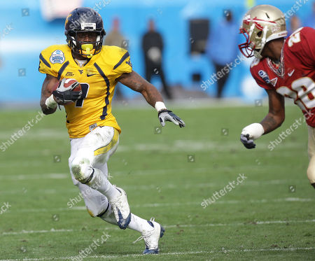 Noel Devine, Jamie Robinson West Virginia running back Noel Devine, left, runs for second quarter yardage as Florida State safety Jamie Robinson, right, moves in to make the tackle during the Gator Bowl NCAA college football game, in Jacksonville, Fla