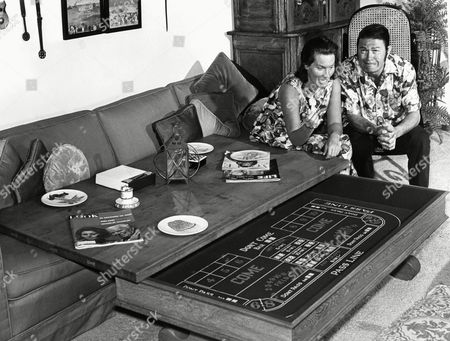 Larry Storch, currently co-starring as Corporal Agarn in ABC-TV?s ?F Troop,? gags it up as his wife, Norma, prepares to roll dice on a gaming table built into their living room coffee table, May 1966. Storch, a former New Yorker, now lives in Hollywood Hills, Calif., to be near the TV and movie studios. A wartime shipmate of Tony Curtis, Storch got into the movie business through Curtis and has since parlayed his wild sense of humor and rubber face into a successful career. Norma, a swimming champion in the late 40?s, once also served as Charlie Chaplin?s assistant at the Circle Theater
