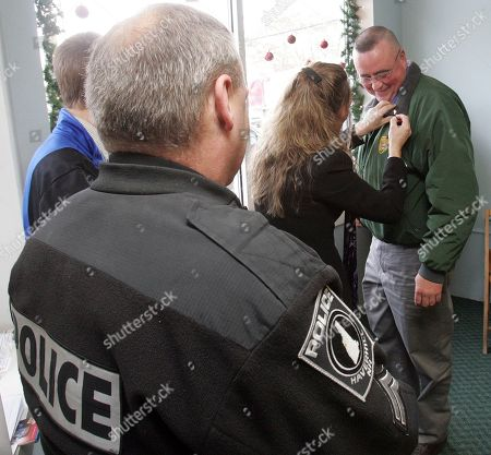 New Hampshire State Police Detective Russ Hubbard gets a pin from Annie Crowley as Cpl Wallace Trott waits his turn for a pin honoring murder victim 25-year-old Christopher Gray, of Groton, Vt in Wells River, Vt., Monday, Dec. 21,2009. Family members held a reception for officers and investigators in the case before sentencing of Timothy Smith, Anthony Howe and Amber Talbot, who pleaded guilty in the death of Gray