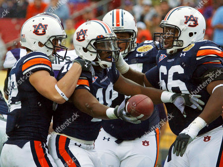 Kodi Burns, Chris Todd, Mike Berry Auburn wide receiver Kodi Burns (18) celebrates with teammates, including Chris Todd, left, and Mike Berry, right, after scoring a first quarter touchdown against Northwestern during the Outback Bowl NCAA college football game, in Tampa, Fla