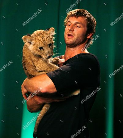 """Dave Salmoni Dave Salmoni who is Animal PlanetÕs large predator expertl, poses with a lion cub named Shera in New York, . SalmoniÕs new show """"Into the Pride"""" premieres this week"""