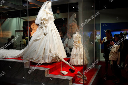 """People look at the wedding dress of Lady Diana Spencer during a preview of the exhibition """"Diana: A Celebration"""" at the National Constitution Center in Philadelphia. The Cincinnati Museum Center will be the last stop on the public exhibition tour for an exhibition about the late Princess Diana from Feb. 14, 2014 to Aug. 17"""