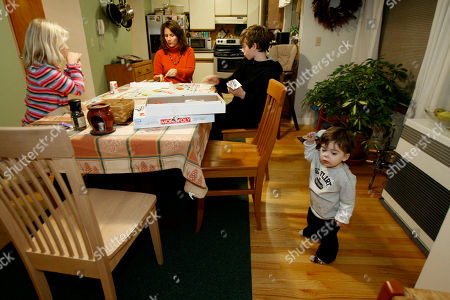 This photo shows Betsy Charlesworth, center, playing with her daughter, Morgan, left, and son, Myles, at Monopoly in their kitchen table in Jericho, Vt. At far right is son, Marty