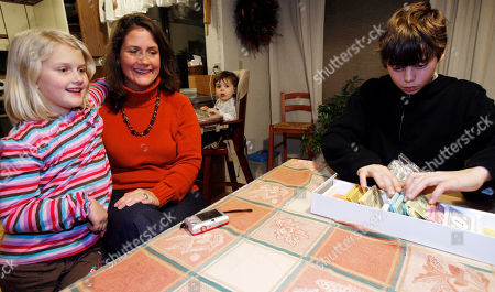 This photo shows Betsy Charlesworth, second from left, sitting with her daughter, Morgan, left, and son, Myles, in their kitchen in Jericho, Vt. At rear is son, Marty