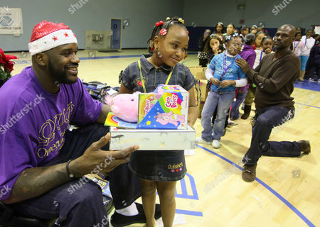 Shaquille O'Neal Cleveland Cavaliers' Shaquille O'Neal gives out a Christmas toy to Stephanie Duhbar at Challengers Boys & Girls Club in Los Angeles