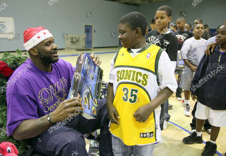 Shaquille O'Neal Cleveland Cavaliers' Shaquille O'Neal, left, gives a Christmas toy to Kevin Winzer at Challengers Boys & Girls Club in Los Angeles, on