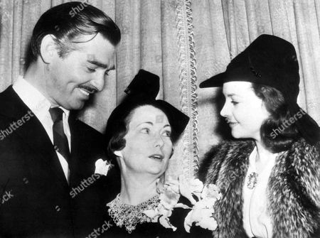 "Stock Photo of Undated photo of American author Margaret Mitchell, centre, who wrote ""Gone With The Wind"", talks with British actress Vivien Leigh, who played Scarlett O'Hara in the film adaption of the book, at a reception somewhere in America. American film actor Clark Gable, who played Rhett Butler in the film, listens to the conversation"