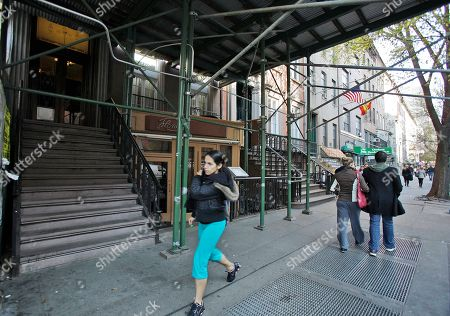 A woman walks beneath scaffolding in the front of a New York City building believed to be home to Rachel Uchitel, a woman reported to be in a romantic relationship with PGA Champion Tiger Woods. Woods was injured early Friday morning after his SUV struck a tree and fire hydrant as he pulled out of his driveway