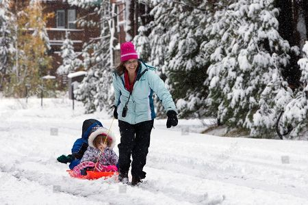Stock Photo of Debbie Kahn, right, pulls her son, Eli, 7, left, and daughter, Talia, 2, McLaughlin through the snow at Serene Lakes, near Soda Springs, Calif. A weekend storm brought rain to Northern California and snow to the Sierra Nevada