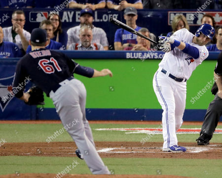 Toronto Blue Jays' Michael Saunders, right, watches his home run off Cleveland Indians relief pitcher Dan Otero during the second inning in Game 3 of baseball's American League Championship Series in Toronto