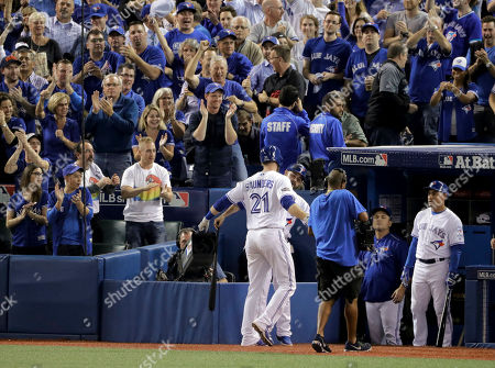 Toronto Blue Jays' Michael Saunders celebrates in the dugout after his home run against the Cleveland Indians during the second inning in Game 3 of baseball's American League Championship Series in Toronto