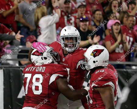 Arizona Cardinals running back David Johnson, center, celebrates his touchdown run with guard Earl Watford (78) and tight end Darren Fells (85) during the first half of an NFL football game against the New York Jets, in Glendale, Ariz