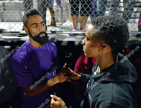 A classmate of Trinity Gay offers his sympathy to her father, Tyson Gay, following a gathering in her memory at Lafayette High School, in Lexington, Ky. Several thousand people turned out Monday night for a candlelight vigil in Kentucky to honor Gay's 15-year-old daughter, Trinity, who was fatally shot over the weekend