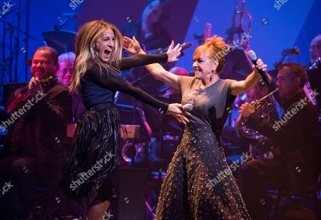 Actress Sarah Jessica Parker, left, embraces singer and actress Andrea McArdle as they perform together during a benefit concert for the Hillary Victory Fund, in New York