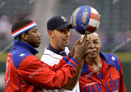 "Anthony Buck Buckets Blake, Curly Neal, David Aardsma Seattle Mariners' David Aardsma, center, is shown how to spin a ball by Harlem Globetrotter basketball players Curly Neal, right, and Anthony ""Buck Buckets"" Blake before a baseball game against the Los Angeles Angels, in Seattle"