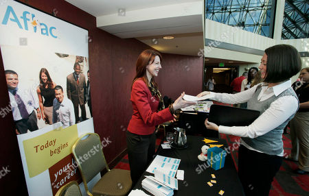 Alison Smith, right, of Coupeville, Wash., hands a resume to Andrea Phaneuf, a special projects coordinator with the Aflac Inc. insurance company, as Smith attends an employment event hosted by National Career Fairs, in Bellevue, Wash. Smith, who has a degree in business administration, recently moved to Washington from New York and was attending her first job fair