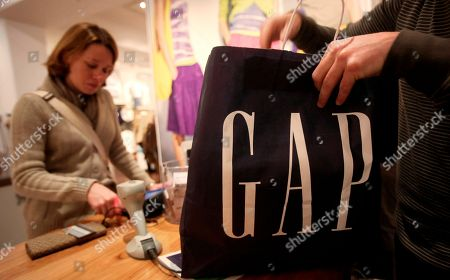 In this photo from, peer advisor Preston Fruge, right, bags clothing purchased by Gabriela Dias, left, from Brazil, at a Gap store in San Francisco