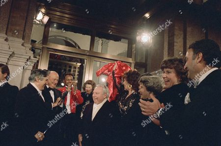 Stock Picture of Carnegie Hall Chairman James D. Wolfensohn, after cutting a ribbon, held by Bess Meyerson, fifth from right, wearing hoop at New York's Carnegie Hall reopening in New York, on Monday, night, December 1986. From left are Wolfensohn, New York's Mayor Edward I. Koch, Stern, with glasses on head, Bess Meyerson, with ribbon, and noted Zubin Mehta, right. Others in photo are unidentified