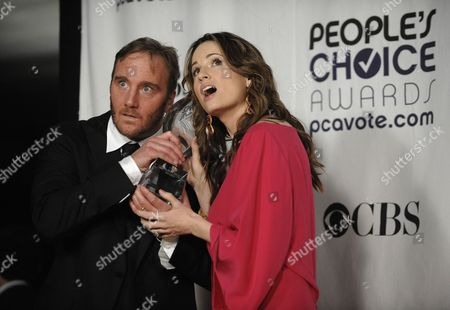 """Jay Mohr, Paula Marshall Jay Mohr, left, and Paula Marshall pose for a photo with their favorite new TV comedy award for """"Gary Unmarried,"""" backstage at the 35th Annual People's Choice Awards on in Los Angeles"""