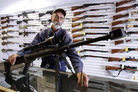 Capitol City Arms Supply owner Steve Swartz shows off a Barrett .50-caliber rifle in Springfield, Ill. The Tennessee Senate, gave final approval to a resolution designating the firearm as the state's official state rifle
