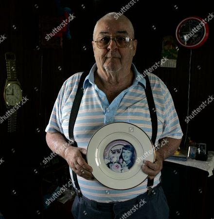 Herman Reber, 74, holds a plate with an image of his daughter, Peggy Lynn Reber, on it in his Lebanon, Pa., home on . The body of his 14-year-old daughter, Peggy Lynn Reber, found murdered in 1968, has been exhumed by investigators looking to solve the 40-year-old mystery