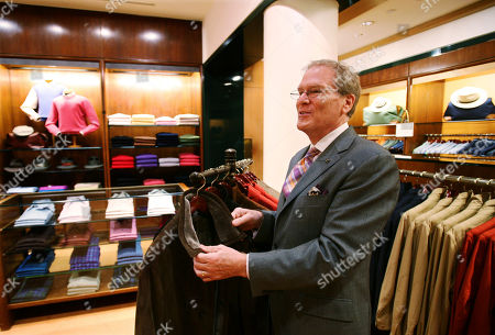 Marc Cohen, a sales associate at Paul Stuart clothing store, talks about an Italian-made car coat on in New York. Retailers are already talking about hefty price hikes of up to 15 percent this year on holiday goods from staples like tree ornaments and toys to luxury goods like Italian-made suits