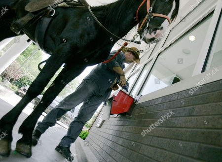 Allan Peerce Allan Peerce's horse Hitman holds steady as Peerce does his banking at a drive through teller in Leitchfield, Ky., . Peerce rides Hitman, adorned with signs of protest, to bring attention to the high cost of fuel