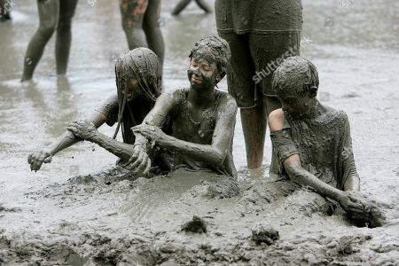 Alyssa Braun, Rachael Natiw, Andy Carr From left, Alyssa Braun, Rachael Natiw and Andy Carr play in the mud during Mud Day sponsored by the Wayne County Parks and Recreation in Westland, Mich., . The annual event allows the children one fun day to frolic in the mud