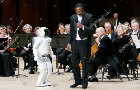 """Thomas Wilkins, ASIMO Detroit Symphony Orchestra Resident Conductor Thomas Wilkins, right, teases Honda's ASIMO robot after it conducted the Detroit Symphony Orchestra performing """"Impossible Dream"""" during a concert in Detroit, . Honda Motor Co. designed ASIMO, which stands for Advanced Step in Innovative Mobility. ASIMO can run, walk on uneven slopes and respond to simple voice commands, but Honda says this is the first time ASIMO has ever conducted an orchestra. ASIMO can't respond to the players, but mimicked the actions of a conductor who was videotaped beforehand"""