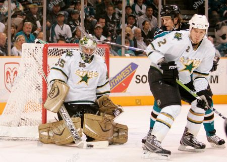 Jeremy Roenick, Marty Turco, Nicklas Grossman Dallas Stars goalie Marty Turco, left, stop a shot on goal as San Jose Sharks center Jeremy Roenick, in blue, and defenseman Nicklas Grossman (2), of Sweden, looks on in the second period of Game 5 of a Western Conference semifinal playoff hockey series in San Jose, Calif