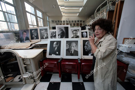 """In this image taken Thursday Aug. 2, 2007, photographer Editta Sherman, then 95, stacks celebrity portraits at her studio residence in New York's Carnegie Hall. The Italian-born Sherman, 98, who photographed famous faces from Monroe and Andy Warhol to Elvis Presley and called the """"Duchess of Carnegie Hall"""" for being its longest resident, was forced from the studio she called home since 1948"""