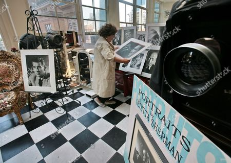 """In this image from Thursday Aug. 2, 2007, Editta Sherman, then 95, stacks photo portraits she made with a giant 100 year old Eastman view camera, right, at her studio residence in New York's Carnegie Hall. The Italian-born Sherman, 98, who photographed famous faces from Monroe and Andy Warhol to Elvis Presley and called the """"Duchess of Carnegie Hall"""" for being its longest resident, was forced from the studio she called home since 1948"""