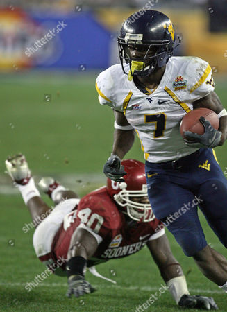 Noel Devine; Curtis Lofton West Virginia running back Noel Devine (7) rushes with the ball for a touchdown ahead of Oklahoma's Curtis Lofton in the third quarter of the Fiesta Bowl college football game, in Glendale, Ariz