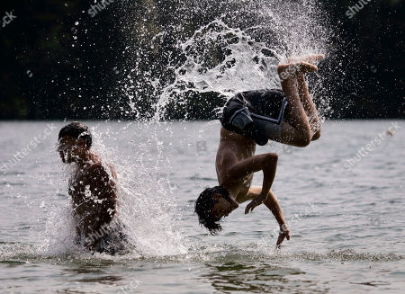Joey Marrero, Freddie Roman Freddie Roman, 13, right, of Waltham, Mass. is flipped into the water from the shoulders of Joey Marrero, 27, also of Waltham, as they keep cool at Walden Pond in Concord, Mass