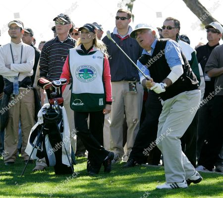 Stock Image of Natalie Gulbis, Ted Forstmann Natalie Gulbis, with golf clubs, left, who plays on the LPGA Tour, watches as amateur Ted Forstmann, right, hits up to the 14th green of the Pebble Beach Golf Links during the first round of the AT&T Pebble Beach National Pro-Am golf tournament in Pebble Beach, Calif. Gulbis was working as Forstmann's caddie. Forstmann, a longtime financier who counted the iconic baseball card company Topps and business jet company Gulfstream Aerospace among his buyouts, died, at the age of 71. The cause was brain cancer, according to a statement from sports agency IMG. Forstmann was the chairman and CEO of IMG and was the senior founding partner of the investment firm Forstmann Little & Co. Forstmann Little bought IMG in 2004